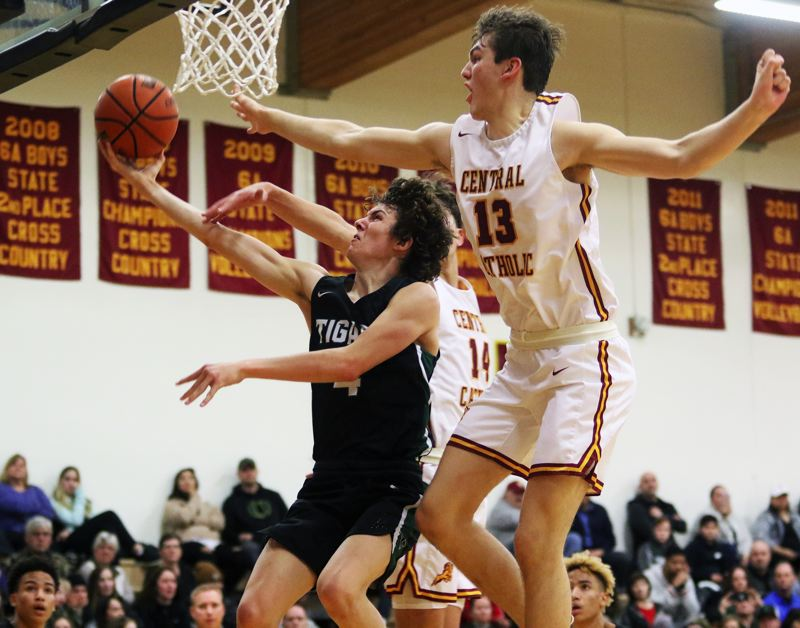 PMG PHOTO: DAN BROOD - Tigard High School junior Brett Moss (left) gets past Central Catholic senior Gaige Ainsile as he goes to the basket during Saturday's Class 6A state playoff contest.