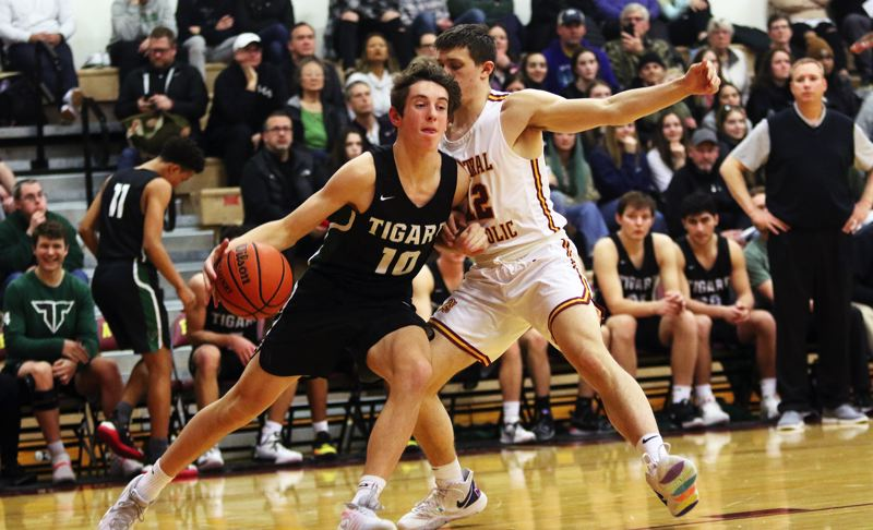 PMG PHOTO: DAN BROOD - Tigard High School junior Jake Wihtol (10) drives the baseline against Central Catholic sophomore Aidan Slater during Saturday's Class 6A state playoff contest.
