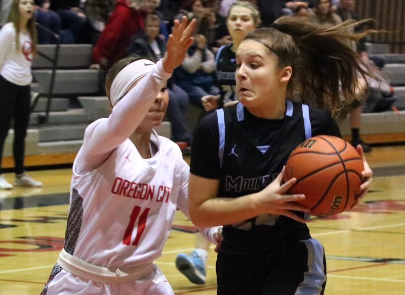 PMG MEDIA PHOTO: JIM BESEDA - Mountainsides Halle Hageman drives to the basket against Oregon Citys Tyra Bradford to score the games first basket;