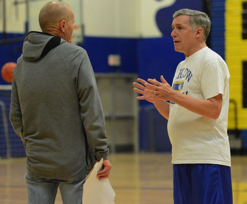 PMG PHOTO: DAVID BALL - Barlows Tom Johnson and assistant Gene Saling (right) compare notes, while players warm up prior to Tuesdays practice.