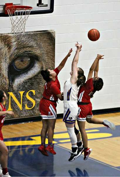 JAYSON SMITH - Seniors Jiana Smith-Francis, left, and Sha'Rita Johns, right, block a Cottage Grove player. Smith-Francis scored four points for Madras, while Johns added 11 points. Madras lost 60-43 March 6 in the 4A state playoffs.
