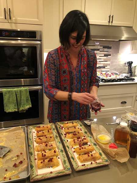 Rebecca Demorest prepares appetizers made of brie and proscuitto, wrapped in phyllo dough which was baked then drizzled with honey and sprinkled with pomegranate arils.