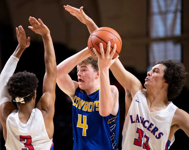 LON AUSTIN/CENTRAL OREGONIAN - Caleb Arnold goes up through a pair of Churchill defenders for two of his eight points as the Cowboys lost to the Lancers in the state quarterfinals. Crook County plays West Albany in the first round of consolation Thursday morning at 9 a.m.