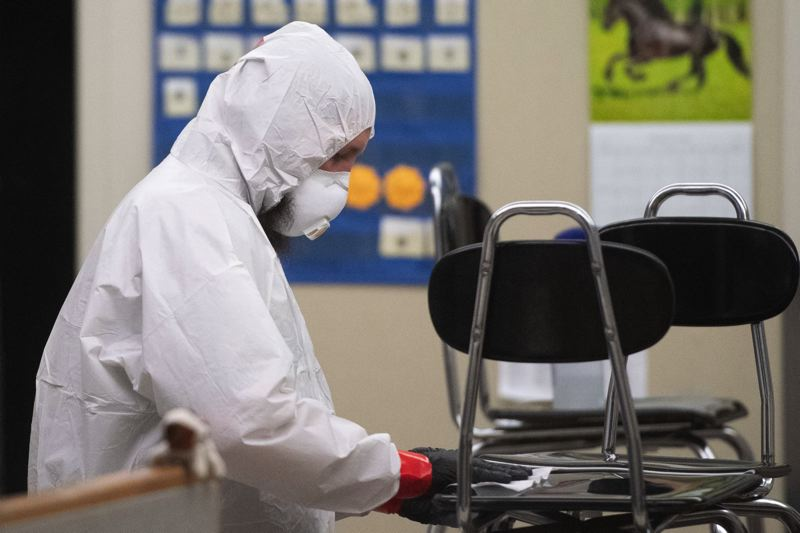 PMG PHOTO: CHRISTOPHER OERTELL - Wearing protective equipment, a worker sanitizes classroom equipment and furniture Sunday evening, March 8, at South Meadows Middle School in Hillsboro.