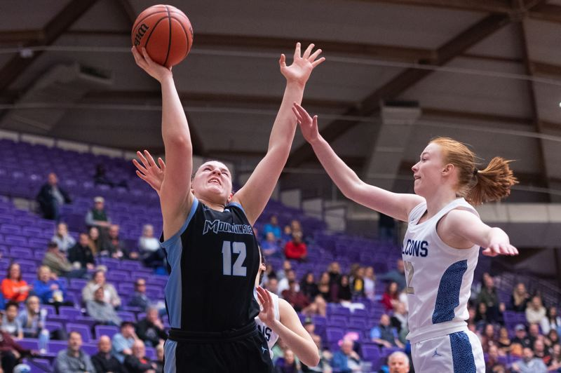 TIMES PHOTO: CHRIS OERTELL - Mountainside's Lindsey Wilson (12) and Liberty's Breeze Bartle (12) during the quarterfinals of the OSAA 6A state girls basketball championship at the Chiles Center on the campus of the University of Portland in Portland, Ore., on Wednesday, March 11, 2020.