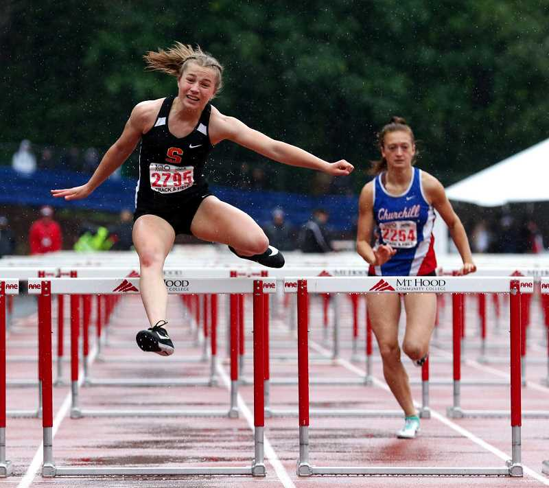 PMG FILE PHOTO - Emma Jones, Scappoose hurdler, battles through a soggy 100 hurdles race en route to a fifth-place finish at state last year.