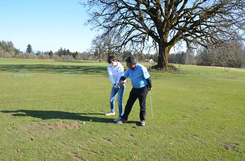 St. Helens boys golf coach Dave Lawrence works with Thatcher Lyman, who is new to the team this season.