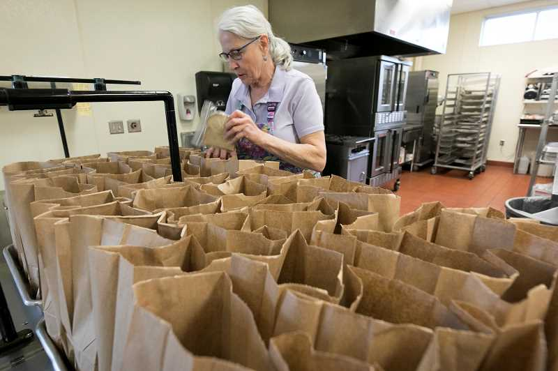 PMG PHOTO: JAIME VALDEZ - Agi Hendriks, the kitchen lead at Tualatin Elementary School, packs lunches for students at the school Friday, March 13. Several school districts will provide take away meals for pick up at designated sites during the state mandated closure.