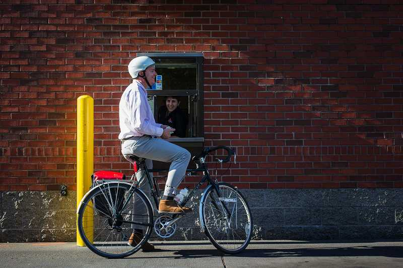 PMG PHOTO: CHRISTOPHER ONSTOTT - Bicyclist Houston Bolles sips his strawberry milkshake in the Burgerville drive-through window during his evening commute in 2013.