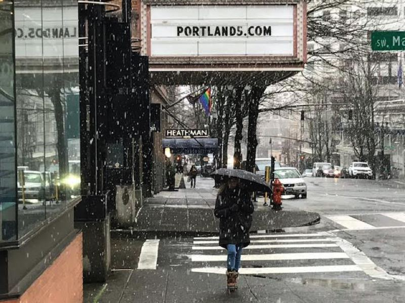 PMG PHOTO: DANA HAYNES - Pedestrians braved the wet snow and fat snowflakes during the late morning flurry, which wasn't sticking to city sidewalks.