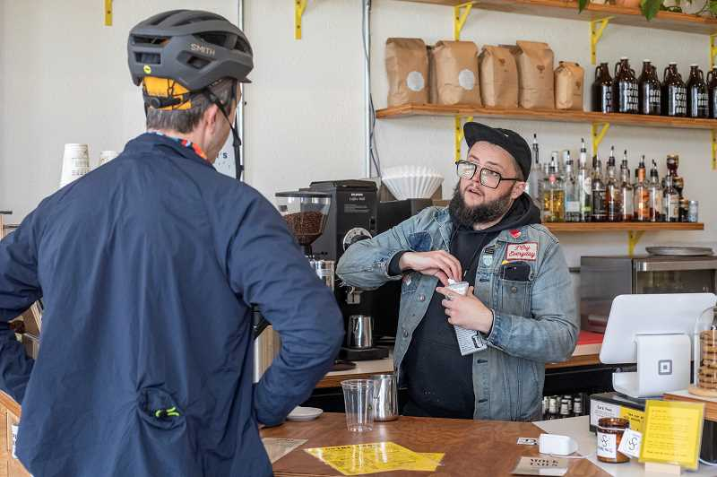 PMG PHOTO: JONATHAN HOUSE - Phillip Stewart prepares a latte in a cup to go for a customer Monday morning at Coffee Beer. Stewart, like many coffee shop owners, says his business will only serve drinks to-go for the time being.