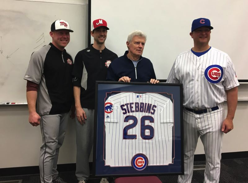 COURTESY PHOTO - Hall of Fame baseball coach Dale Stebbins is presented with a Chicago Cubs jersey while surrounded by former players (from left) Bryan Donahue, Brian Burres and Gabe Sandy.