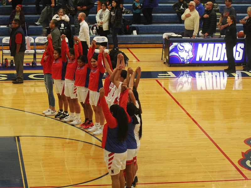 STEELE HAUGEN - The Madras Lady Buffalo basketball team raises their hands after the National Anthem. The team finished with a 15-9 overall record.