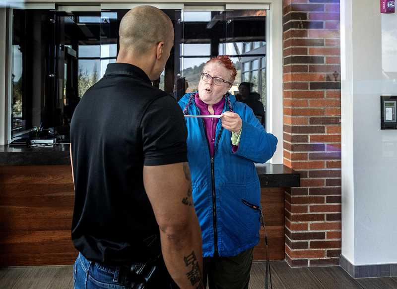 PMG PHOTO: JONATHAN HOUSE - Concerned Citizens of West Linn cofounder Abby Farber gives a letter to Police Sgt. Oddis Rollins containing a list of requested reforms from the department.