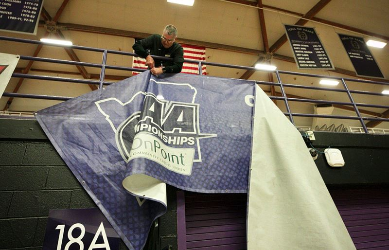 PMG PHOTO: JAIME VALDEZ - The OSAA's Oz Osburn takes down a banner at the Class 6A state basketball tournament at the Chiles Center on the University of Portland campus after concerns about the novel coronavirus led the OSAA to cancel the event Thursday, Marsh 12.