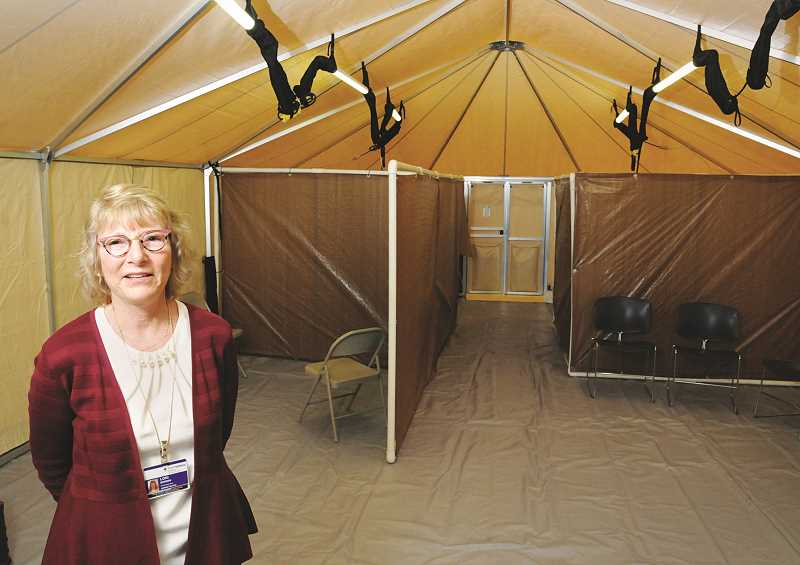 GRAPHIC PHOTO: GARY ALLEN - Lori Bergen, chief executive at Providence Newberg Medical Center, stands in a special tent erected outside the facility's emergency department for intake of patients diagnosed with the coronavirus.