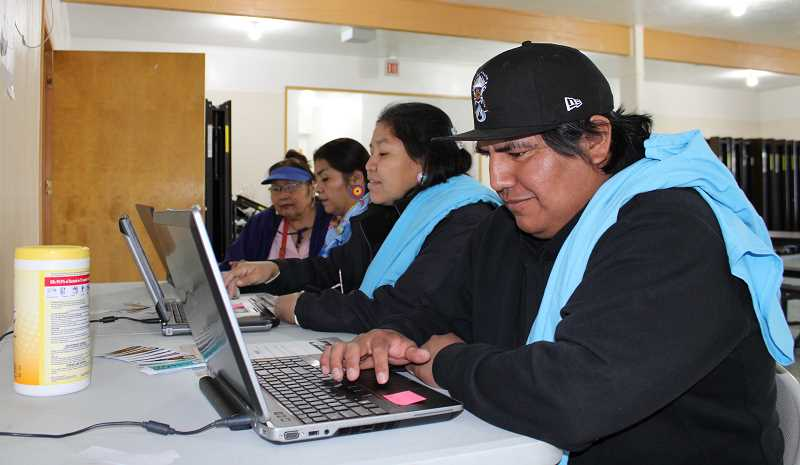 TERESA JACKSON/MADRAS PIONEER - From front, Timothy Kalama, Janice Suppah, Brigette McConville and Brenda Scott fill out the census online at the Agency Longhouse in Warm Springs Thursday, March 12, at a kickoff ceremony. They have census T-shirts thrown over the shoulders.