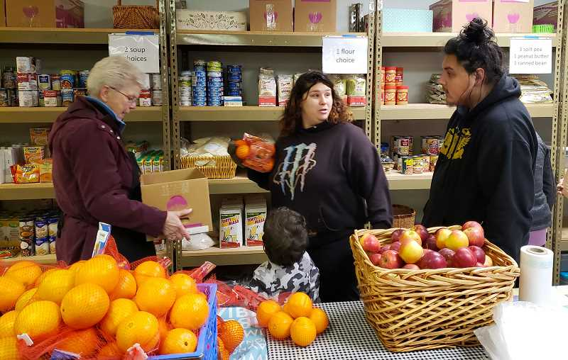 PMG PHOTO: RENDLEMAN, RAYMOND - Gladstone Food Pantry volunteer Sandie Kiehl, left, helps a family choose free groceries during Gladstones Adopt-a-Family event. Food pantries across the state are having to adjust as they try to limit the spread of the novel coronavirus