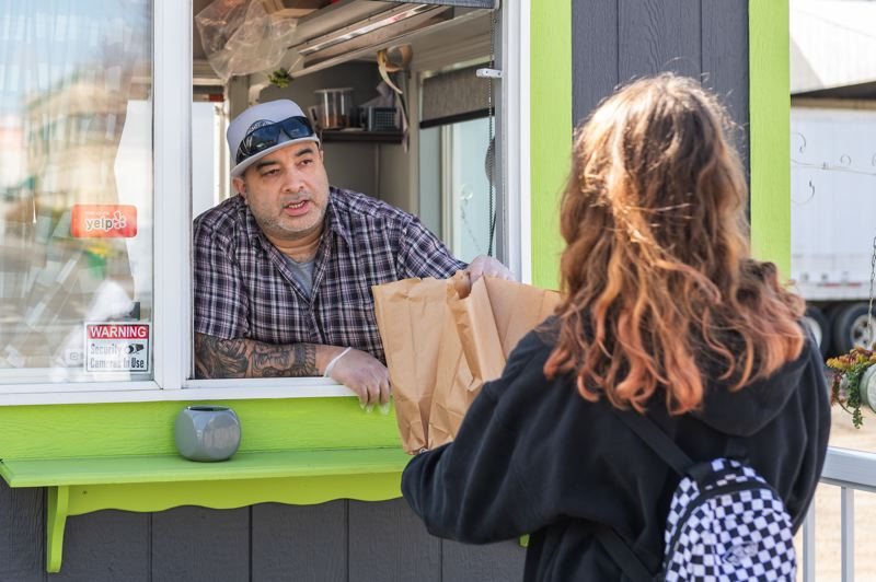 PMG PHOTO: CHRISTOPHER OERTELL - Jose Cassady, owner of Forest Grove Sandwich Shop, hands free sandwich bags to a child on Wednesday, March 18 as part of his efforts to help kids affected by school closures as a result of the spread of the novel coronavirus.