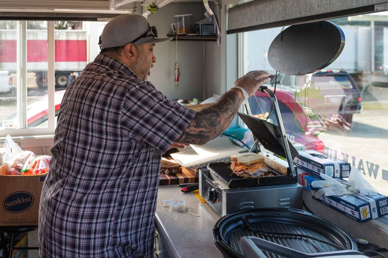 PMG PHOTO: CHRISTOPHER OERTELL - Jose Cassady, owner of Forest Grove Sandwich Shop, makes a sandwich on Wednesday, March 18 at his food truck located at 1821 Main St.