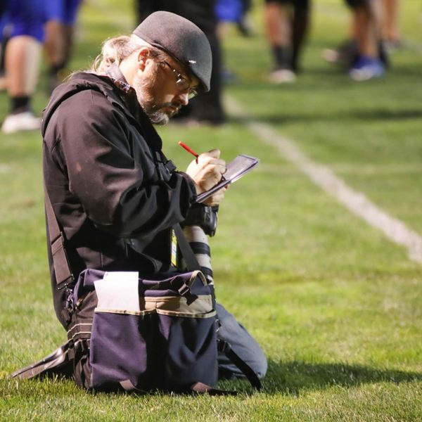 PMG FILE PHOTO - Woodburn Independent Editor Phil Hawkins works the sidelines at a local high school football game. He's one of nearly 200 Pamplin staffers producing news stories as the COVID-19 virus rages.