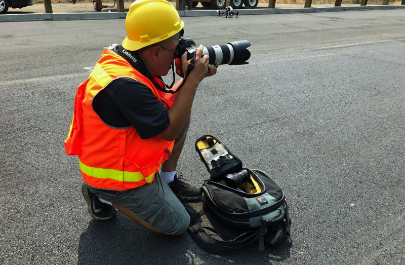 PMG PHOTO: DANA HAYNES - Photojournalist Jaime Valdez covering the opening of a new road in Washington County.