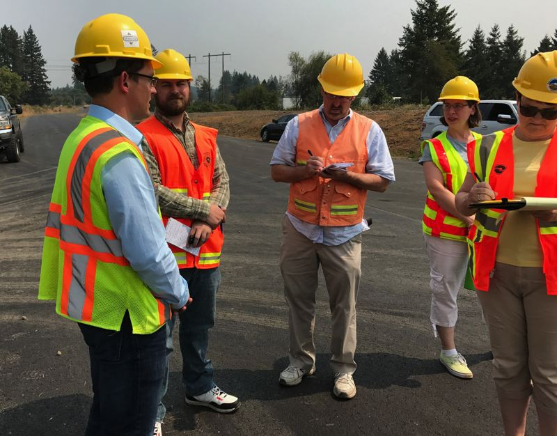 PMG PHOTO: DANA HAYNES - Editor Mark Miller (second from left) and reporter Ray Pitz (center) talking to Oregon Department of Transportation and Washington County officials.