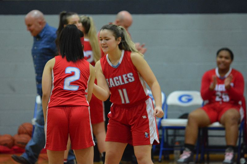 PMG PHOTO: DAVID BALL - Centennials Trinity Miller (11) is greeted by teammate Quynh Vu during pre-game introductions. The Eagles will play an independent schedule the next two seasons.