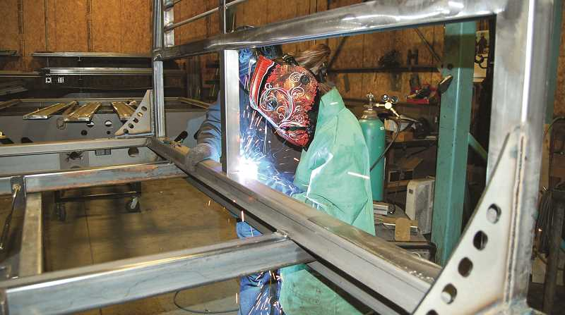 RAMONA MCCALLISTER - Rose Waibel puts a series of welds on a flatbed truck bed, as mentor Joel Lowden looks on.