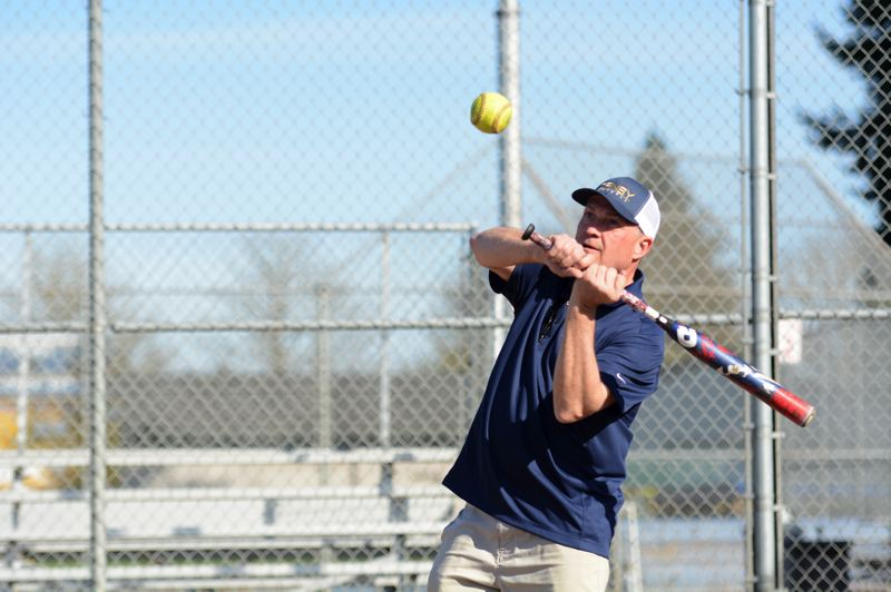 PMG PHOTO: DEREK WILEY - Canby softball coach Ty Kraft hits a fly ball at practice on March 10.