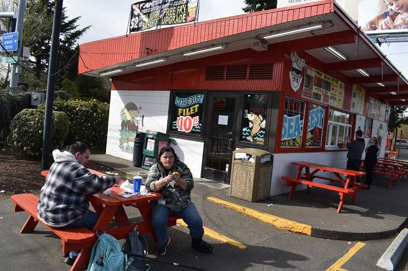 PMG PHOTO: RAYMOND RENDLEMAN - Milwaukie residents Allen and Cheryl Kellerhals eat at Mike's Drive-In on a picnic table in front of the restaurant this week following the ban on dining inside restaurants in Oregon.