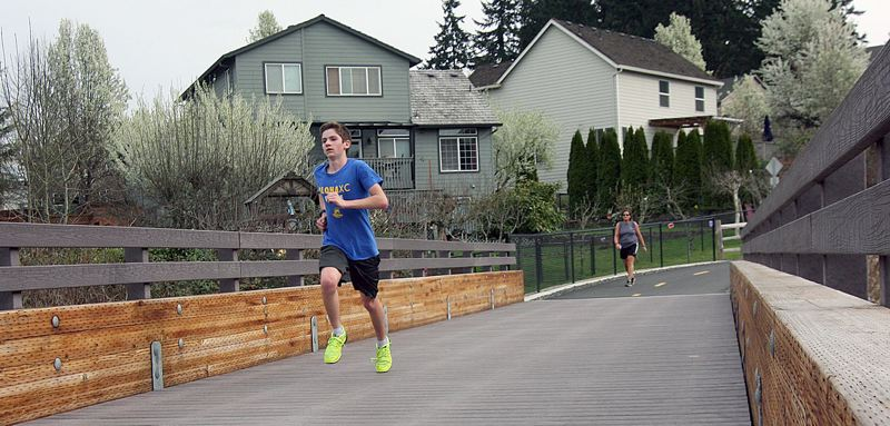 PMG PHOTO: MILES VANCE  - Ian Bake runs across a bridge on the Westside Trail between Southwest Rigert Road and Flagstone Drive in Beaverton. Trails in the Tualatin Hills Park & Recreation District are staying open, but playgrounds and exercise equipment are closed.