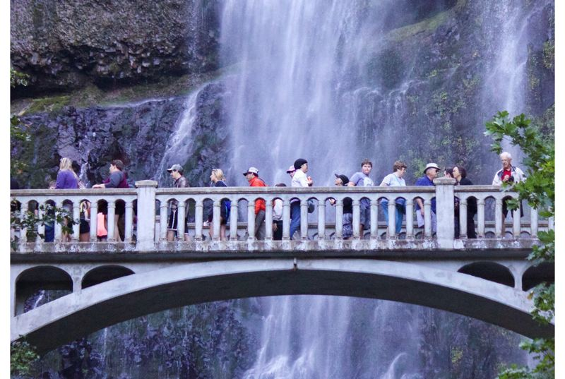 FILE PHOTO - Visitors cross the bridge at Multnomah Falls in 2017.