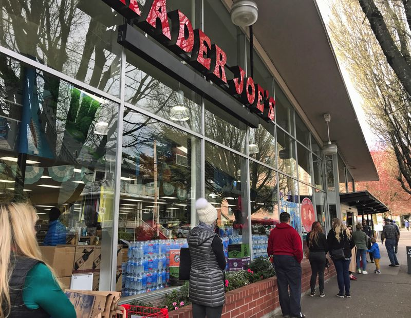 PMG PHOTO: DANA HAYNES - Customers wait outside a Northwes Portland Trader Joe's on Saturday, March 21, all six feet apart, and wait for other customers to finish their shopping before entering.