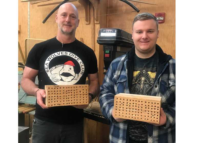 COURTESY PHOTO - Rodney Shroufe, a science teacher at Clackamas High School, accepts a donation of five mason-bee houses from sophomore Reed Carty.