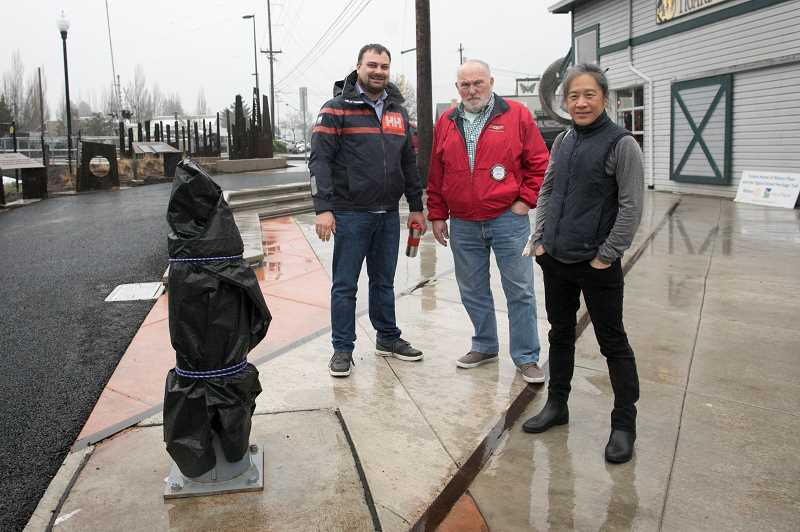 PMG PHOTO: JAIME VALDEZ - Brandon Petersen, left, Marland Henderson and Suenn Ho stand next to the stanchion base where the Rotary Plaza clock and post will be installed March 29 next to Symposium Coffee as part of the Tigard Street Heritage Trail and Outdoor Museum