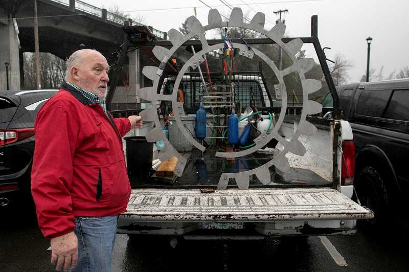 PMG PHOTO: JAIME VALDEZ - Marland Henderson, a former member of the Tigard City Council and a local contractor, displays the one-quarter-inch-thick stainless steel, Rotary International geared wheel that will encircle the clock in Rotary Plaza.