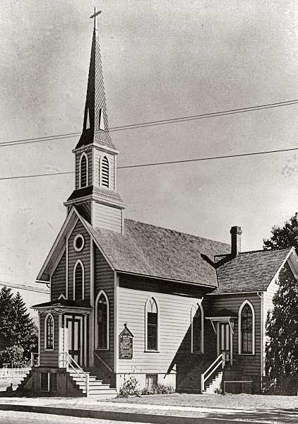 SMILE COURTESY PHOTO - During its tenure as Milwaukies St. Johns Episcopal Church, the 1851 building was moved four times - the last time, aboard a barge that took it down the river to Sellwood! This photo shows the old church back in 1920, at 20th and S.E. Jefferson in Milwaukie. Today, in Sellwood as Oaks Pioneer Church, it no longer has the double entryway, or the shed room with the chimney at the right of the photo.