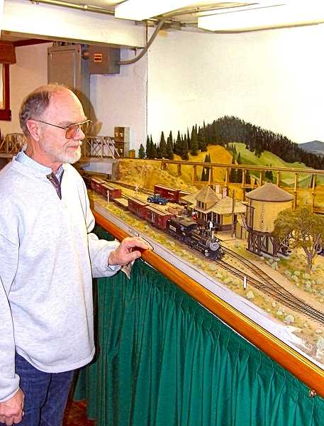 DANA BECK - Meet Jim Reardon, builder of the St. Johns Episcopal Church scale model - here shown standing over a small section of the model railroad layout he has built in his basement. He has won various awards for his detailed craftsmanship in making the buildings, railroad stations, and train cars models for it. Its not surprising that he was asked to build a model of the historic, original St. Johns Church.