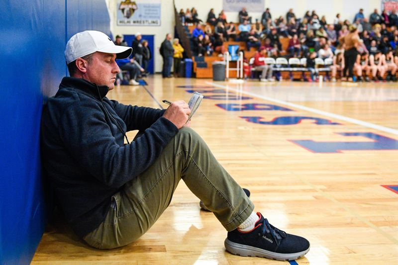 PMG FILE PHOTO - Wade Evanson, sports editor of the News-Times, takes notes on the sidelines of a basketball game.