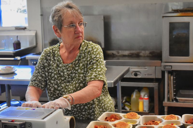 PMG PHOTO: EMILY LINDSTRAND - A volunteer at the Estacada Community Center prepares food to be delivered through Meals on Wheels, which is still operating during the COVID-19 outbreak.