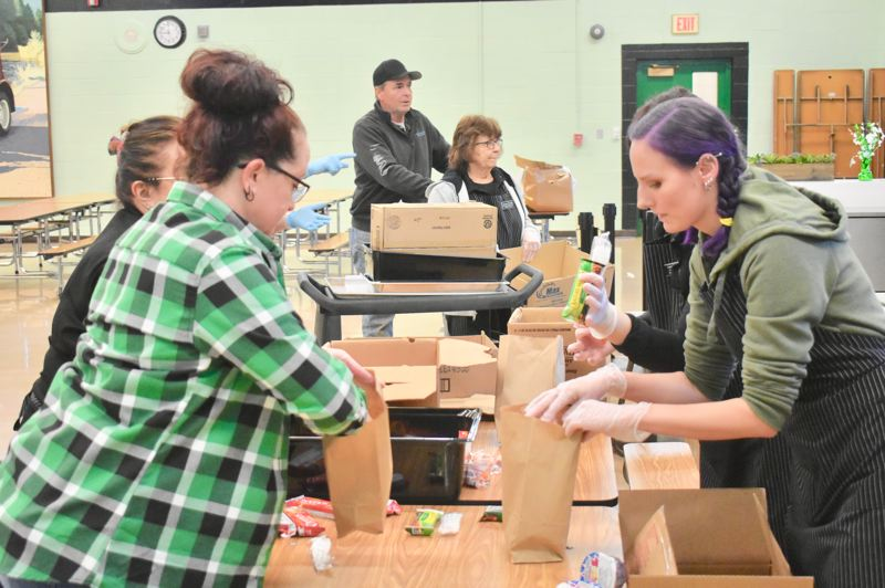 PMG PHOTO: EMILY LINDSTRAND - Estacada School District staff prepare meals to be distributed to students. Though school buildings are closed because of the COVID-19 pandemic, food for students is still available.