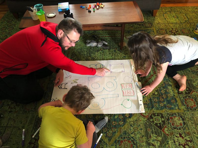 COURTESY PHOTO: THE GALLAGHER FAMILY - The Gallagher kids work on their Bs with dad as a way to keep learning while schools are closed until April 28. The closures are part of the effort to stop the spread of the novel coronavirus.