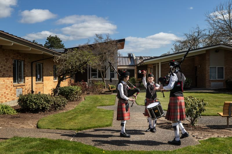 PMG PHOTO: JONATHAN HOUSE - From left, Adelynn Williams, Abigail Plopper and Stephen Plopper of the Portland Metro Youth Bagpipe Band perform outside Maryville Memory Care in Beaverton on Saturday, March 21.
