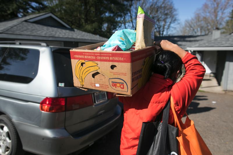 PMG PHOTO: JAIME VALDEZ - A woman brings home a box of food prepared by volunteers with the Foundation for Tigard-Tualatin Schools.