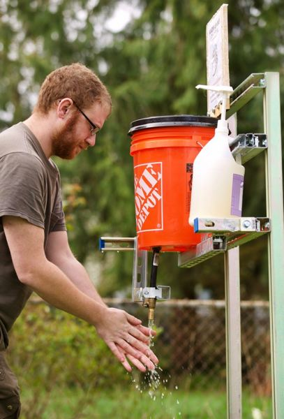 PAMPLIN MEDIA GROUP: JAIME VALDEZ - Apprentice electrician Jesse Harwin quit work to to to be more helpful to his north Portland community, and started by building a handwashing station on his front lawn.