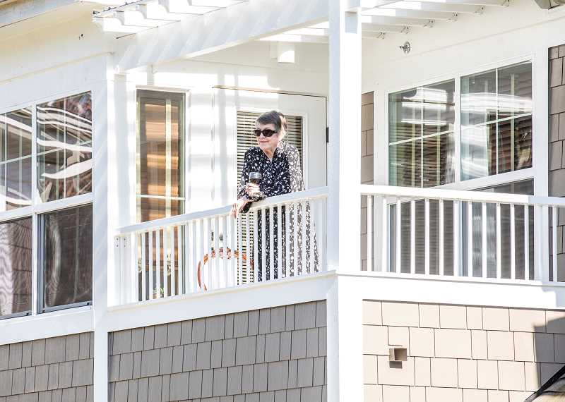 PMG PHOTO: JONATHAN HOUSE - Anne Loemken enjoys the Friday afternoon concert with a glass of wine on her balcony at Stafford Retirement Community.
