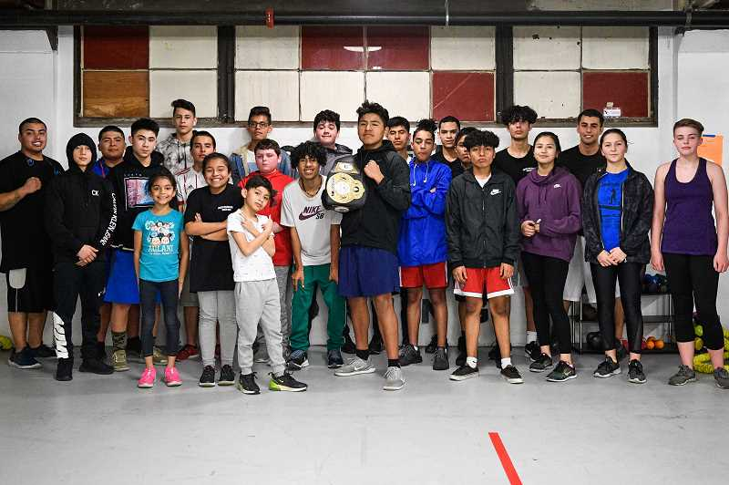 PMG PHOTO: CHRISTOPHER OERTELL - Ricardo Marquez (center), a Silver Gloves boxing champion, holds his belt while being surrounded by other boxers before a workout at Chief Cornerstone Boxing in Hillsboro.