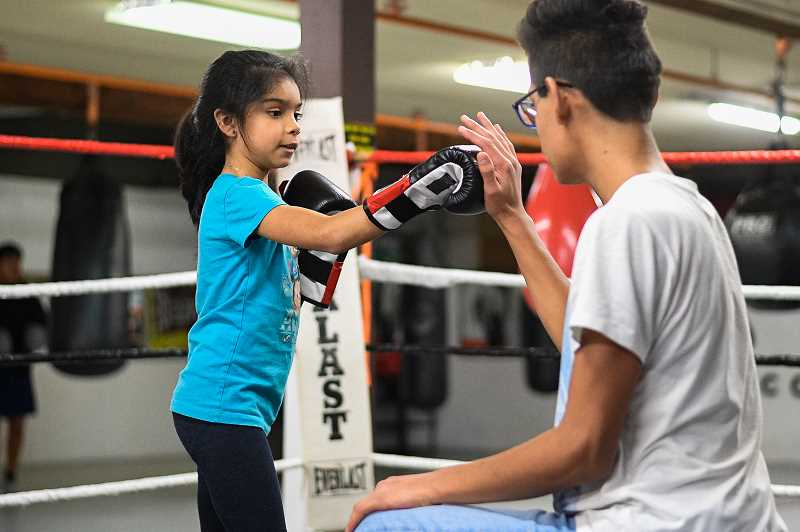 PMG PHOTO: CHRISTOPHER OERTELL - Abamare Gutierrez, 8, gets some boxing tips from Joel Delariva, 14, during a workout at Chief Cornerstone Boxing in Hillsboro.