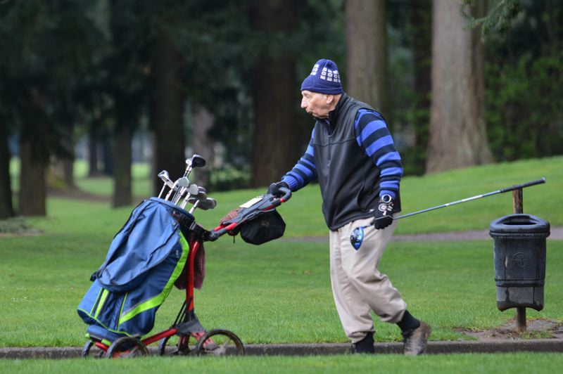 PMG PHOTO: DAVID BALL - A golfer makes a solo round on the eastside course at Glendoveer on Wednesday morning. Notice the disabled ball-washer in the background — one of the measures courses are taking to limit touch points.